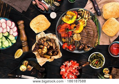 Grill table concept. Different foods cooked on the grill on the wooden table grilled steak and grilled vegetables top view