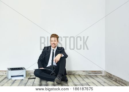 Happy elegant man with earphones and touchpad sitting by wall