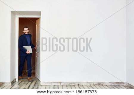 Young ceo with touchpad entering room or office