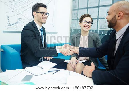 Two happy businessmen handshaking with female colleague near by
