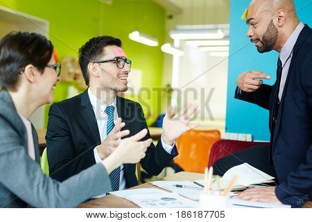 Modern colleagues playing humorous game with sticky notepapers