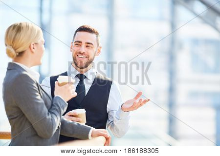 Portrait of two successful business people, man and woman, smiling and talking talking during break in gass hall of modern building, both holding coffee cups