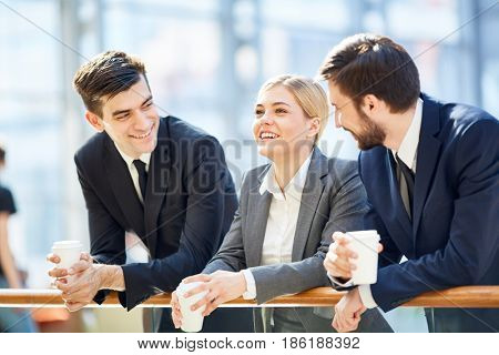Portrait of three business people, one woman and two men, smiling cheerfully while chatting in glass hall of modern office building leaning on railing and holding coffee cups