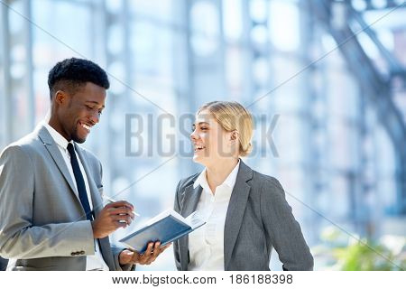 Portrait of two young business colleagues, one of them African,  discussing work smiling cheerfully  standing in glass hall of modern office building