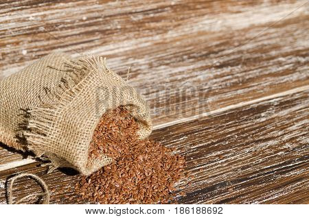 Brown flax seeds in the sacking bag on wooden background space for text. Superfood: linseeds are high in omega-3 fatty acids essential for good health. Healthy eating vegan diet concept.
