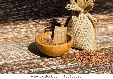 Brown flax seeds and sacking bag on wooden background space for text. Superfood: linseeds are high in omega-3 fatty acids essential for good health. Healthy eating vegan diet concept.copy space