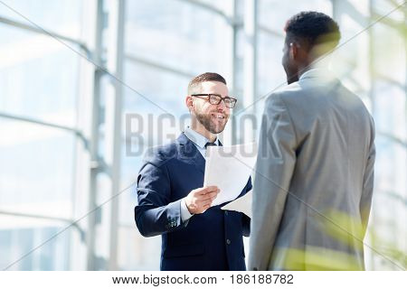 Portrait of successful businesman smiling while handing documents to African-American partner standing in modern glass hall of office building