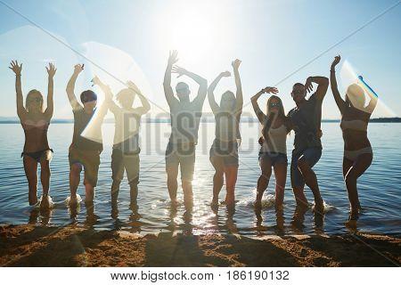 Energetic friends dancing in water by sandy beach