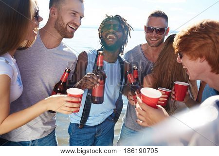 Laughing intercultural friends with beer having beach party