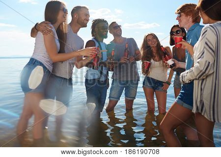 Young buddies with beer standing in water and talking