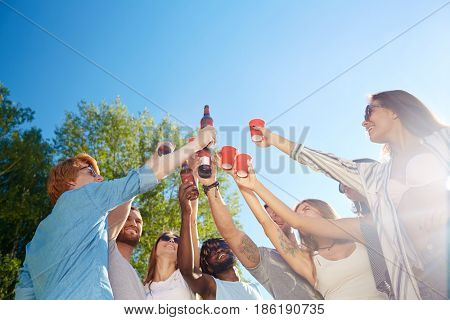 Ecstatic buddies with drinks raising hands while cheering up