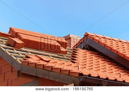 roof under construction with stacks of red ceramic roof tiles ready to fasten