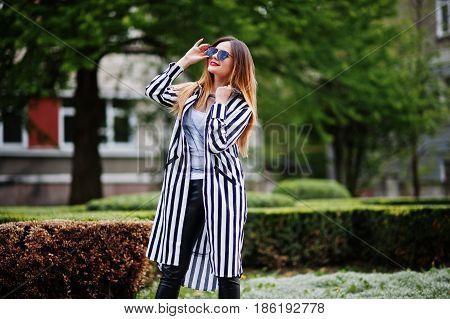 Fashionable Woman Look With Black And White Striped Suit Jacket, Leather Pants And Sunglasses Posing