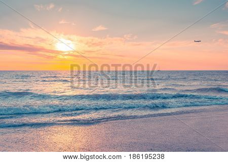 Waves at sunset with boat and plane on background on a warm evening South Australian coast. Pastel color tones.