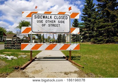 A sign indicating a sidewalk is closed due to construction.
