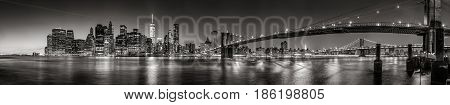 Panoramic Black and white view of Lower Manhattan Financial District skyscrapers at twilight with the Brooklyn Bridge and East River. New York City