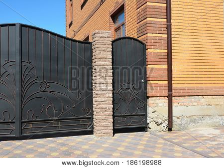Metal fence door installation. Installation of Stone and Metal Fence with Door and Gate.