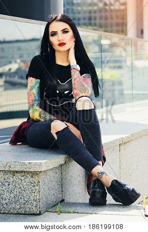Gothic Tattoo Fashion. Full-length Shot Of Beautiful Tattoed Hipster Girl Posing To Camera While Sit