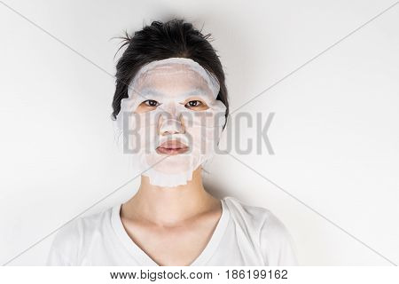 Asian girl with facial paper masking for beauty on white background
