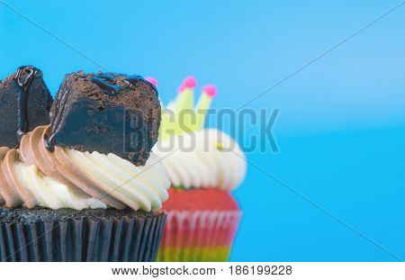 2 cupcakes chocolate and rainbow cupcake on blue background copy space