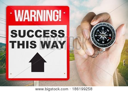Holding compass for the way to success warning concept signage