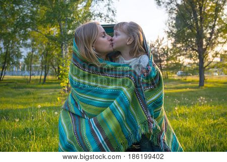 Happy Mother And Little Daughter, Wrapped In A Blanket, Are Kissing In A Park