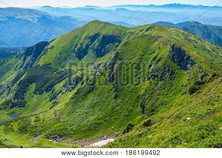 Picturesque Green Ridge Against The Background Of Mountains
