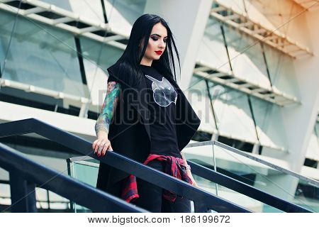 Urban Gothic Woman. Portrait Of Attractive Tattoed Hipster Girl Standing Against Urban Background.