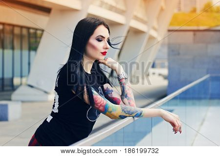Tattoed Beauty. Portrait Of Attractive Tattoed Hipster Girl Standing Against Urban Background.