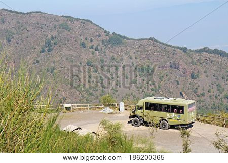 POMPEII, ITALY - October 9 2014: Bus of the Busvia del Vesuvio tours parked at the base of the trail for hiking to the top of the cinder cone of the volcano Mount Vesuvius, south of Naples, Italy.