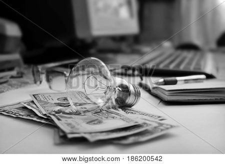 photography with scene of the light bulb lying on dollar as metaphore financial business to ideas in monochrome colour