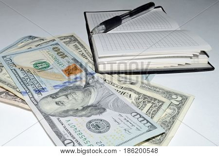 photography with scene of the notepad, pen and dollars to subjects financial business planning