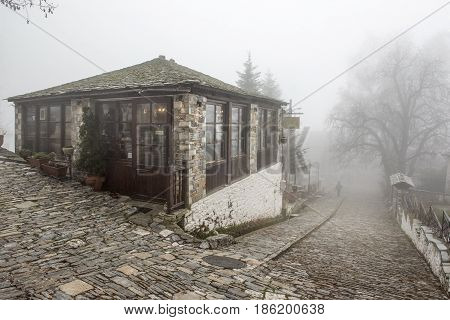 Fog and traditional stone building in Vizitsa village on mountain Pelion.Greece