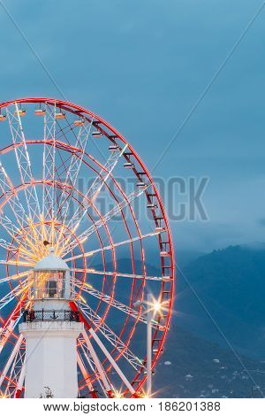 Batumi, Adjara, Georgia. Close View Of The Ferris Wheel And Top Part Of The Old White Lighthouse In Its Center. Blue Evening Sky And Mountainous Hazy Waves Background.