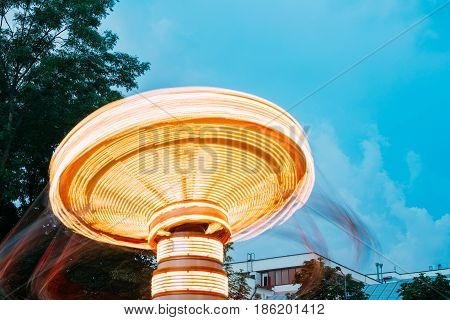 Top Disk Part Of Brightly Illuminated, Dynamic Energy Rotating High Speed Carousel Merry-Go-Round With Blurred Motion Effect Around. Blue Evening Sky Background. Summer Evening In City Amusement Park