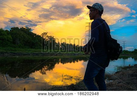 Labuan,Malaysia-May 7,2017:Young man fishing with bait casting in the river during colourful sunset clouds in the Labuan island,Malaysia.