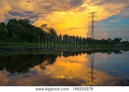 High voltage electric transmission tower with reflection in the river during golden hour sunset.
