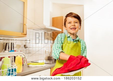 Portrait of happy kid boy standing in the kitchen and wiping dry plate with red towel