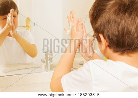 Portrait of little boy washing his hands with soap and looking in the mirror