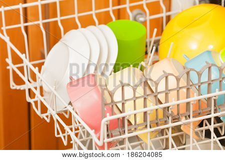 Close-up picture of opened dishwasher with clean plates and colored bowls on its rack