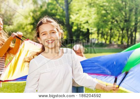 Close-up portrait of happy Caucasian girl waving colorful parachute with her friends outdoor in spring
