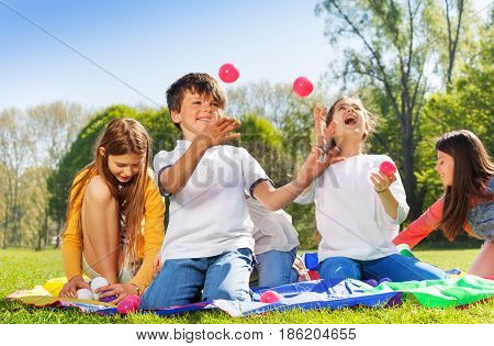 Portrait of happy kids sitting on the grass in the park and juggling with colorful balls
