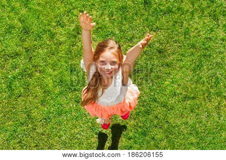 Top view portrait of happy ten years old girl jumping on the grass with hands up