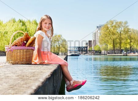 Side view picture of adorable blond girl sitting on embankment with picnic basket against urban landscape