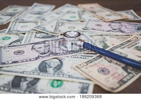 Stethoscope On Dollar Banknote Money On Wooden Background