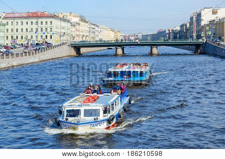 SAINT PETERSBURG RUSSIA - MAY 1 2017: Excursion boats on Fontanka River near Semyonovsky bridge. Unidentified tourists are visiting sights during walk along rivers and canals of city