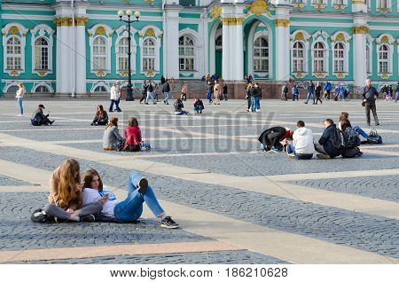 SAINT PETERSBURG RUSSIA - MAY 1 2017: Unknown young people rest on Palace Square near State Hermitage Museum (Winter Palace) on sunny spring day St. Petersburg Russia