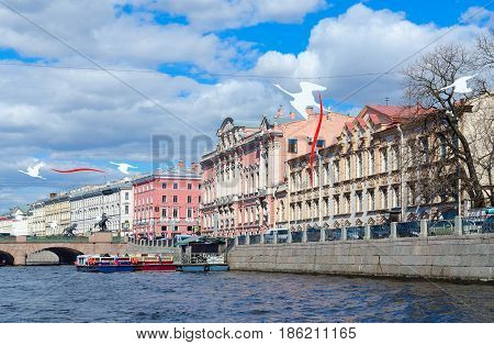 SAINT PETERSBURG RUSSIA - MAY 3 2017: Excursion ships on Fontanka River near Anichkov Bridge in St. Petersburg. Unknown tourists are going to see sights during walk along rivers and canals of city