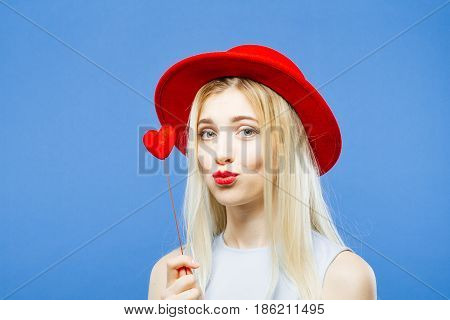 Cute Girl with Hat and Little Red Heart in Hands is Grimacing Looking at the Camera on Blue Background in Studio. Valentines Day Concept.