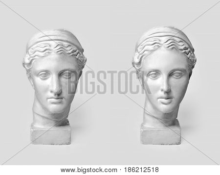 Two marble heads of young women, ancient Greek goddess bust before plastic surgery and after operation on light background. Old and new beauty standarts concept